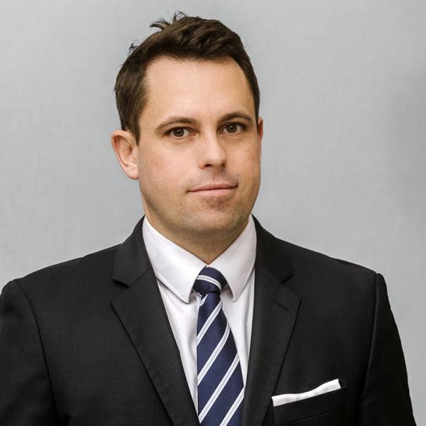 Rechtsanwalt Magister Hertzberg blickt in die Kamera